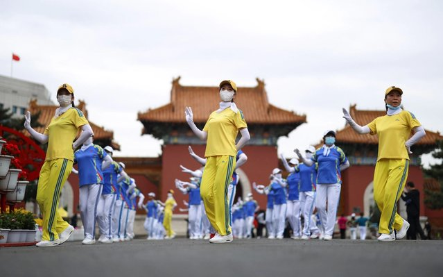 People wearing face masks dance at a park in Shenyang, in China's northeastern Liaoning province on May 15, 2020. (Photo by AFP Photo/China Stringer Network)