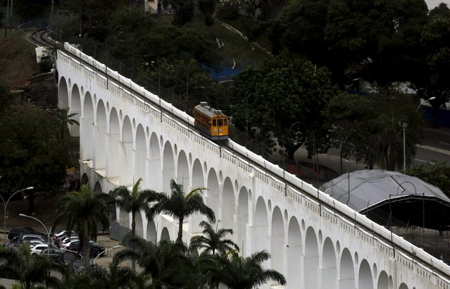 "A ""bonde"" (tram) is seen on a line over the Arcos da Lapa (Lapa Arches), an old aqueduct from the colonial era, in the Santa Teresa neighborhood of Rio de Janeiro, Brazil, September 9, 2015. The Santa Teresa bonde, called ""Bondinho"" in Portuguese, is running with passengers as a part of a test period, after the service was suspended in 2011 following an accident that killed six people, according to residents. (Photo by Pilar Olivares/Reuters)"