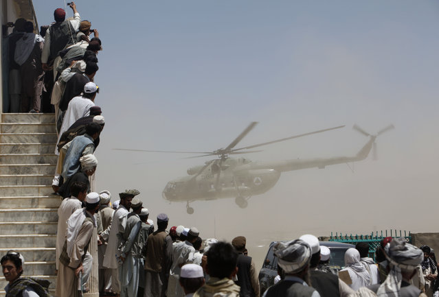 A crowd watches an Afghan National Army Air Corps helicopter carrying President Hamid Karzai during an election rally in Gardez, capital of Paktia province, south of Kabul August 4, 2009. (Photo by Ahmad Masood/Reuters)