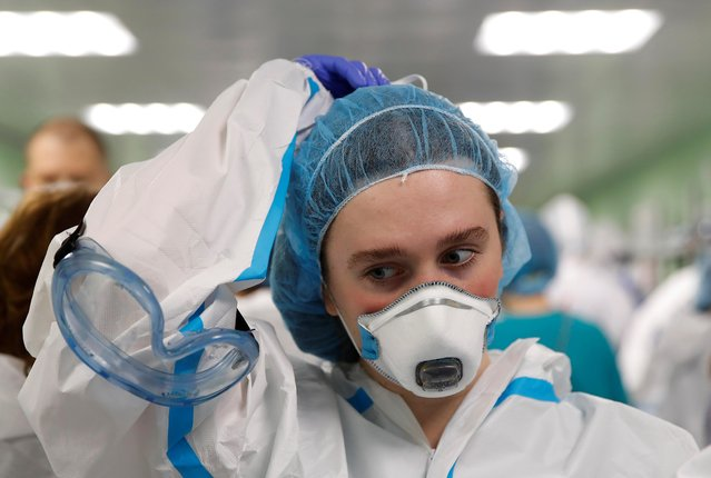 A medical specialist puts on personal protective equipment (PPE) at the City Clinical Hospital Number 15 named after O. Filatov, which delivers treatment to patients infected with the coronavirus disease (COVID-19), in Moscow, Russia on May 25, 2020. (Photo by Maxim Shemetov/Reuters)