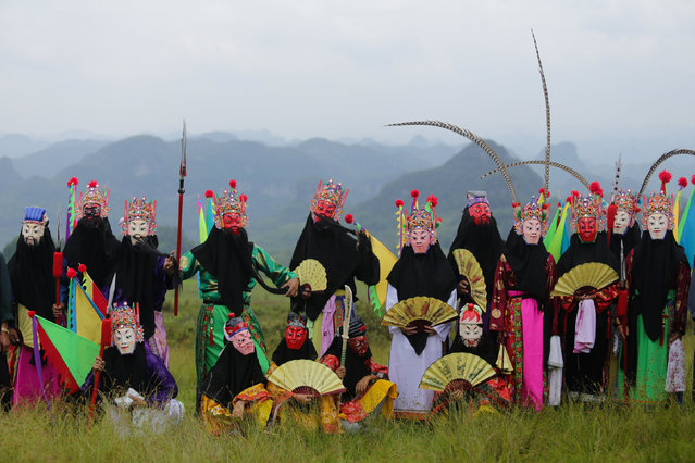 Participants wearing traditional costumes pose for pictures before performing in a local opera during the beginning of autumn, according to the lunar calendar, in Qiannan, Guizhou Province, China, August 7, 2016. (Photo by Reuters/Stringer)
