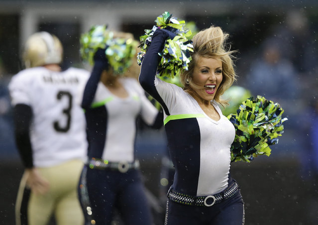 Seattle Seahawks Sea Gals cheerleaders perform before an NFC divisional playoff NFL football game against the New Orleans Saints in Seattle, Saturday, January 11, 2014. (Photo by Elaine Thompson/AP Photo)