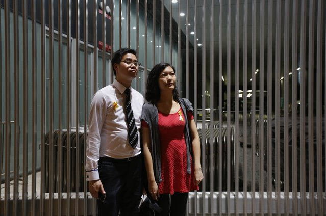 """Terrence Tang (L), 28, a businessman, and his girlfriend Jacqueline Cheung, 30, a social worker, pose for a photograph at a rally ahead of an """"Occupy Central"""" civil disobedience protest in Hong Kong September 26, 2014. Tang said, """"I am not keen on Occupy Central but I oppose those unreasonable argument against the movement"""". (Photo by Bobby Yip/Reuters)"""