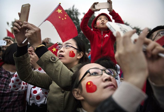 Chinese tourists take pictures near Tiananmen Square on the 65th National Day on October 1, 2014 in Beijing, China. The day marks the founding of the People's Republic of China on October 1, 1949. (Photo by Kevin Frayer/Getty Images)