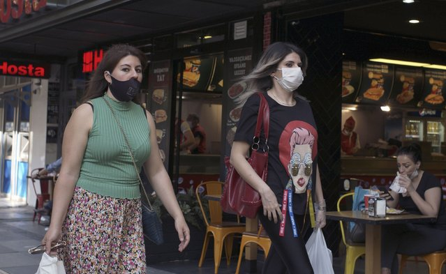 Women wearing face masks to protect against the spread of coronavirus, walk in the city centre, in Ankara, Turkey, Wednesday, June 24, 2020. Turkish authorities have made the wearing of masks mandatory in three major cities to curb the spread of COVID-19 following an uptick in confirmed cases since the reopening of many businesses. (Photo by Burhan Ozbilici/AP Photo)