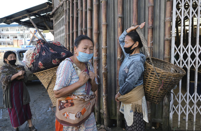 Naga women wear masks as a precaution against the coronavirus and walk past closed shops early morning in Kohima, capital of the northeastern Indian state of Nagaland, Tuesday, June 30, 2020. Several Indian states have reimposed partial or full lockdowns to stem the spread of the coronavirus. (Photo by Yirmiyan Arthur/AP Photo)