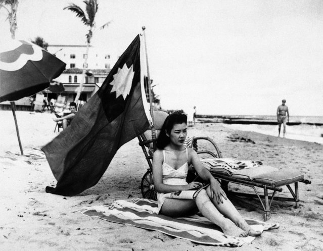 Ruth Lee, hostess at a Miami Chinese restaurant, is seen December 15, 1941. She didn't want to be mistaken for Japanese when she sunbathed on her days off, so she brought along a Chinese flag.  Miss Lee was actually American-born. (Photo by Associated Press)