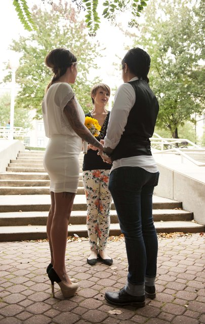 Amanda Scott (L) and Christina Corvin (R) are married by Jessica Milicevic outside the Mecklenburg County Register of Deeds office in Charlotte, North Carolina, October 13, 2014. Monday was the first day that Mecklenburg County issued marriage licenses to gay couples. (Photo by Davis Turner/Reuters)