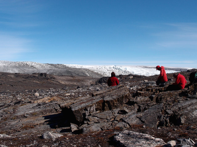 In this photo provided by Laure Gauthiez, taken in July 2012, a field team examine rocks in Greenland. Scientists have found what they think is the oldest fossil on Earth, a remnant of life from 3.7 billion years ago when Earth's skies were orange and its oceans green. In a newly melted part of Greenland, Australian scientists found the leftover structure from a community of microbes that lived on an ancient seafloor, according to a study in Wednesday, August 31, 2016 journal Nature. (Photo by Laure Gauthiez/The Australian National University via AP Photo)