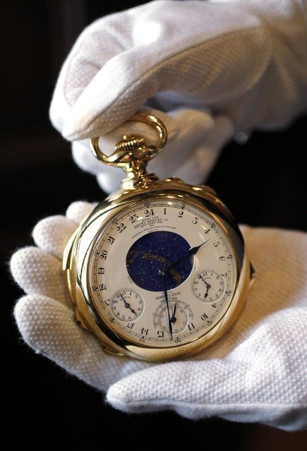"""A staff member holds """"The Henry Graves Supercomplication"""" handmade watch by Patek Philippe which was completed in 1932 at Sotheby's auction house in London October 21, 2014. (Photo by Suzanne Plunkett/Reuters)"""