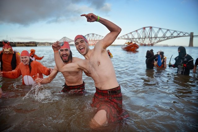 Over 1,000 New Year swimmers, many in costume, braved freezing conditions in the River Forth in front of the Forth Rail Bridge during the annual Loony Dook Swim on January 1, 2013 in South Queensferry, Scotland. Thousands of people gathered last night to see in the New Year at Hogmanay celebrations in towns and cities across Scotland.  (Photo by Jeff J. Mitchell)