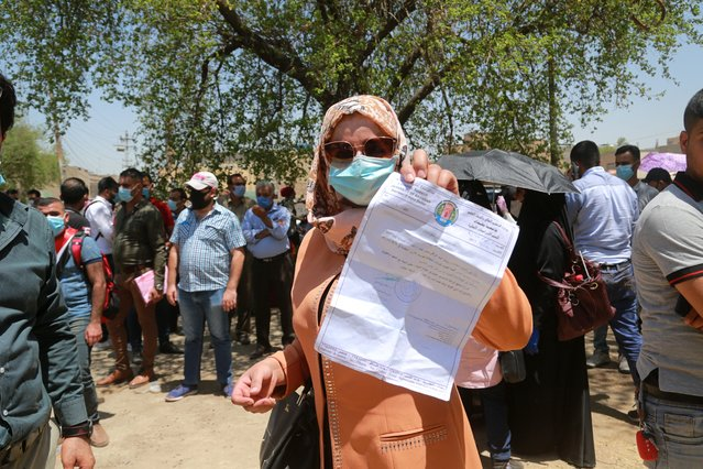 Rowaida Abdul Rahman shows her science master's degree certificate while jobless graduates gather in front of the Ministry of Oil to demand jobs in Baghdad, Iraq, Monday, July 20, 2020. In the Mideast, wave after wave of war, disease and economic collapse leaves this generation feeling hopeless. (Photo by Hadi Mizban/AP Photo)
