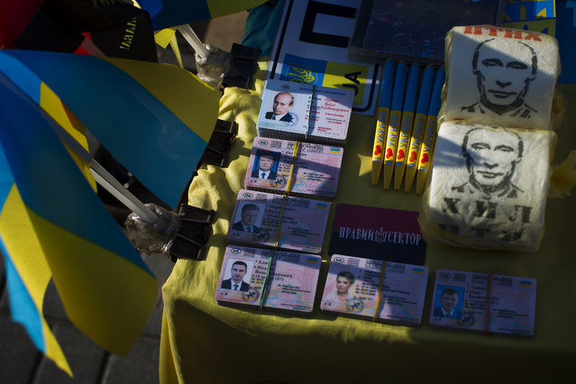 Toilet paper printed with the image of Russian President Vladimir Putin, at right, and fake ID cards with the identity of the main politicians in Ukraine are displayed for sale on a stand in Kiev's Independence Square, Ukraine, Monday, October 27, 2014. Two pro-European parties that campaigned for tough reforms to battle corruption shared the lead Monday after Ukraine's parliamentary election, according to partial results. (Photo by Emilio Morenatti/AP Photo)