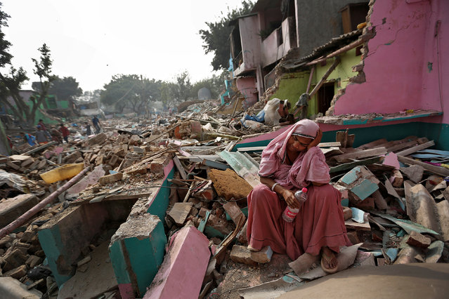 A woman reacts amid the rubble of her home in a slum which was razed to the ground by local authorities in a bid to relocate the residents, Delhi, India, November 2, 2017. (Photo by Cathal McNaughton/Reuters)