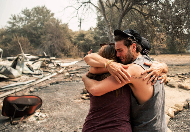 Resident Austin Giannuzzi cries while embracing family members at the burned remains of their home during the LNU Lightning Complex fire in Vacaville, California on August 23, 2020. Firefighters  battled some of California's largest-ever fires that have forced tens of thousands from their homes and burned one million acres, with further lightning strikes and gusty winds forecast in the days ahead. (Photo by Josh Edelson/AFP Photo)