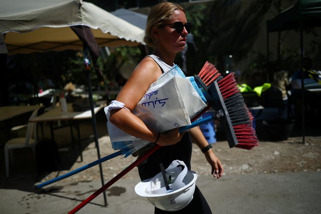 "A volunteer carries equipment through a volunteer base camp that was set up to lead relief and rehabilitation in the aftermath of a massive explosion in Beirut port, Lebanon, August 17, 2020. Survivors now face the mammoth task of rebuilding damaged homes and businesses amid an economic crisis that has left them unable to access their savings. Other volunteer groups, like those at the so-called ""Basecamp"" in Mar Mikhael neighbourhood, have their roots in a wave of popular protests that began in October 2019 against state corruption and mishandling of the economy. (Photo by Hannah McKay/Reuters)"