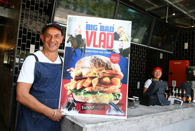 "Burger shop owner Balwinder Kalley holds a poster promoting the ""Big Bad Vlad"" burger which is for sale during this weekend's G-20 summit in Brisbane, Australia, Friday, November 14, 2014. From ""The Big Bad Vlad"" to the ""Obamarama Burger"", local restaurants and pubs are cashing in on the event by offering G-20-themed goodies. (Photo by Tertius Pickard/AP Photo)"