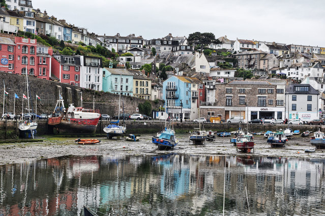 """Runner-up. """"We recently visited Brixham harbour and I was captivated by the colourful houses surrounding it, and their reflection in the water. They were such a bright contrast to the dreary day"""". MICK RYAN, JUDGE: """"A harbour village on a dull day. Who needs the sun with these understated but wonderful pastel tones? No overuse of the saturation 'wow' slider for this photographer. Complex scenes such as these are hard to frame and compose but this is expertly and thoughtfully done, with clean edges and distinct foreground, middle ground and background"""". (Photo by Brenda Melaniphy/The Guardian)"""