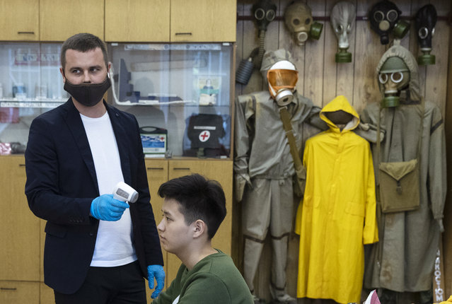 A teacher measures students' temperature before the start of classes in a school, with the chemical protection suits in the background at a school in Moscow, Russia, Monday, September 7, 2020. Russian schools, which switched to online classes in late March when the coronavirus pandemic swept the country, have reopened this month. (Photo by Pavel Golovkin/AP Photo)