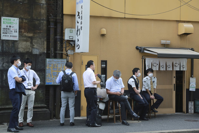 People wearing face masks to protect against the spread of the coronavirus wait to enter a Japanese restaurant for lunch in Tokyo, Tuesday, September 15, 2020. (Photo by Koji Sasahara/AP Photo)