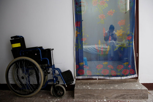 Wang uses a mobile phone as she take a rest in her room at the accommodation where patients and their family members stay while seeking medical treatments in Beijing, China, June 23, 2016. Wang, who suffers from cervical cancer, came from Inner Mongolia to seek treatment at a specialist hospital in Beijing. (Photo by Kim Kyung-Hoon/Reuters)