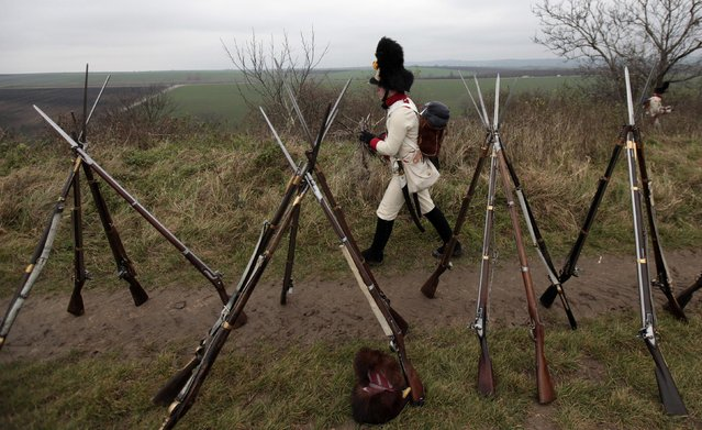 A historical re-enactment enthusiast dressed as a soldier walks past rifles near the southern Moravian village of Herspice November 28, 2014. (Photo by David W. Cerny/Reuters)