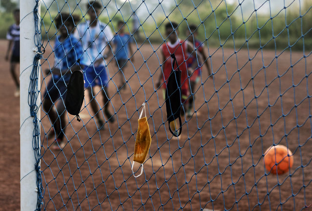 Children hang their face masks in the nets and play a game of soccer during the COVID-19 pandemic in Kochi, Kerala state, India, Tuesday, October 6, 2020. India is the second worst-nation in terms of confirmed coronavirus caseload. (Photo by R.S. Iyer/AP Photo)