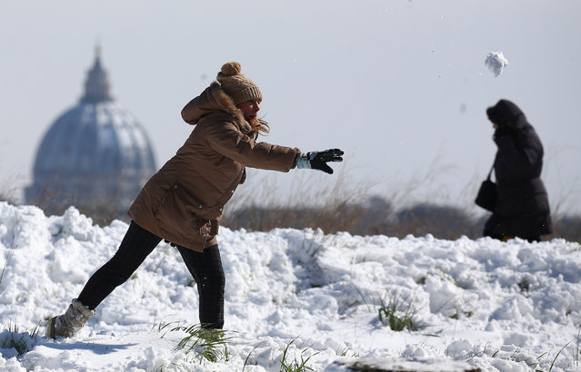 A woman throws a snowball as Saint Peter's Basilica dome is seen in the background after a heavy snowfall in Rome, Italy on February 26, 2018. (Photo by Alessandro Bianchi/Reuters)
