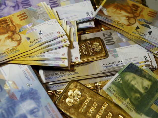 Gold bars and Swiss Franc banknotes are seen in this illustration picture taken at the GSA in Vienna November 13, 2014. Swiss voters looked set November 30, 2014, to clearly reject proposals that would have forced the central bank to buy up massive amounts of gold and imposed strict limits on immigration, threatening close economic ties to the European Union. (Photo by Leonhard Foeger/Reuters)