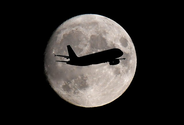 A passenger plane passes in front of the moon as it makes its final landing approach to Heathrow Airport in London, Britain on September 12, 2019. (Photo by Toby Melville/Reuters)