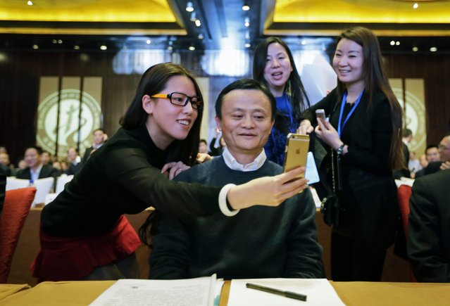 "A female delegate takes a ""selfie"" with Alibaba Group Executive Chairman Jack Ma as he arrives for the Fifth Conference of Zhejiang Chamber of Commerce in Beijing, December 6, 2014. Ma was awarded Honorary Chairman of Zhejiang Chamber of Commerce during the conference. (Photo by Jason Lee/Reuters)"