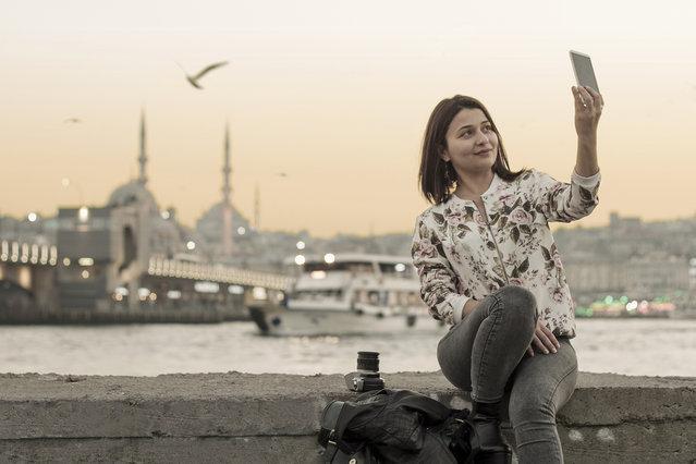 Galata Bridge and Eminönü district in Istanbul. Pretty girl taking a selfie in Istanbul,Turkey. (Photo by Deniz Bayram/Getty Images/iStockphoto)