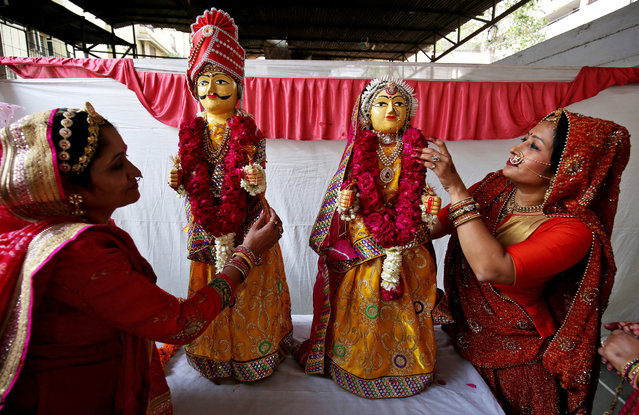 Women adorn wooden idols of a bride and a groom during Gangaur festival, during which unmarried women observe a fast for a desirable husband, while married women do so for the welfare, health and longevity of their husbands, in Ahmedabad, March 14, 2018. (Photo by Amit Dave/Reuters)