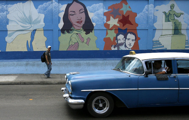 A vintage car used as a cab drives past a mural in Havana, April 26, 2008. (Photo by Claudia Daut/Reuters)