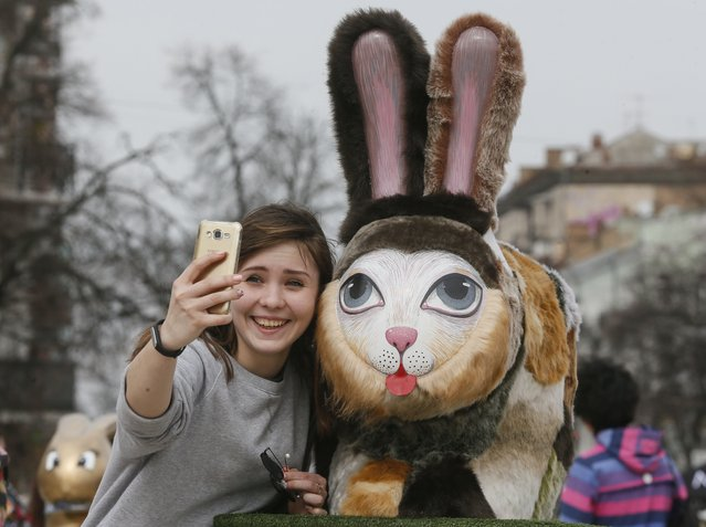 A young girl takes selfie with Easter rabbit sculpture during the Easter eggs (Pysanka) and rabbit exhibition in front of St. Sophia Cathedral in Kiev, Ukraine, 05 April 2018. Ukrainians will mark Orthodox Easter on 08 April 2018, according to Julian calendar. (Photo by Sergey Dolzhenko/EPA/EFE/Rex Features/Shutterstock)