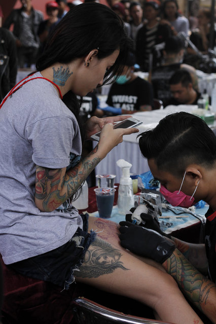 A girl chats on her smartphone as she gets a tattoo on her leg during Bandung Body Art Festival at in Bandung, West Java, on December 7, 2014. (Photo by Rezza Estily/JG Photo)