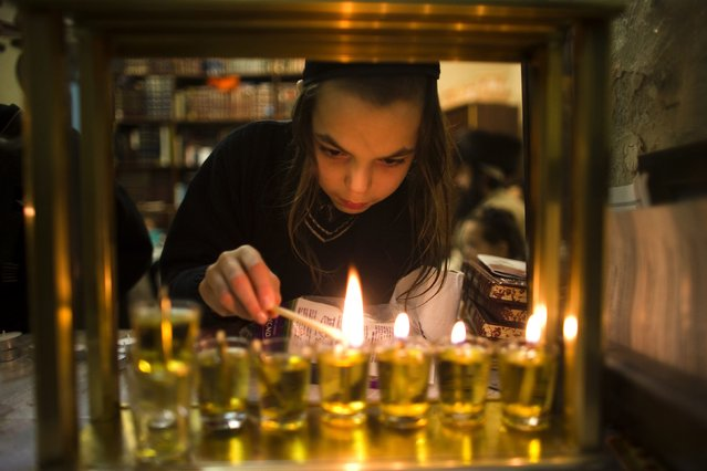 An ultra-Orthodox Jewish boy from the Krois family lights candles for the Jewish holiday of Hanukkah at is house in Jerusalem's Mea Shearim neighbourhood December 22, 2014. (Photo by Ronen Zvulun/Reuters)