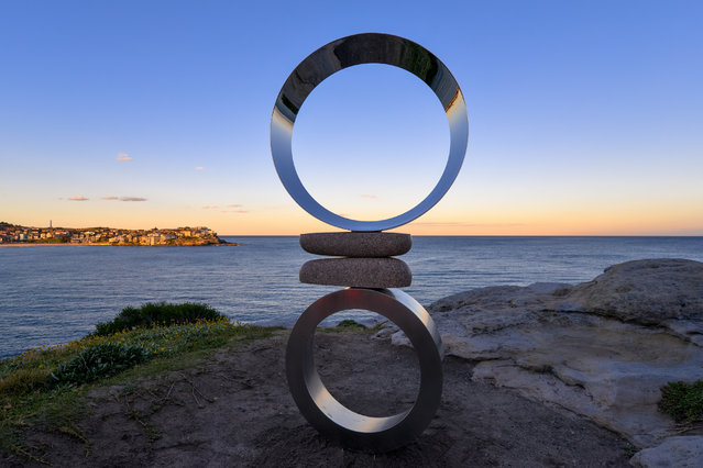 """A whale breaching in the background of """"Mountains Air-Circles"""" by Koichi Ishino at """"Sculpture By The Sea"""" at Bondi Beach on October 19, 2016 in Sydney, Australia. (Photo by Clyde Yee)"""