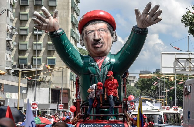 Supporters of Venezuelan President Nicolas Maduro display a giant inflatable dummy depicting late President Hugo Chavez, during demonstration in Caracas on October 18, 2016. Venezuela's Supreme Court has raised another obstacle to an opposition drive for a referendum on recalling leftist President Nicolas Maduro, who is blamed for a deepening economic and political crisis. (Photo by Juan Barreto/AFP Photo)