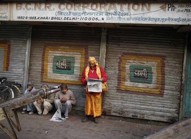 A Sadhu, or a Hindu holy man, reads a newspaper along a roadside in a market on a cold winter morning in the old quarters of Delhi December 31, 2014. (Photo by Ahmad Masood/Reuters)