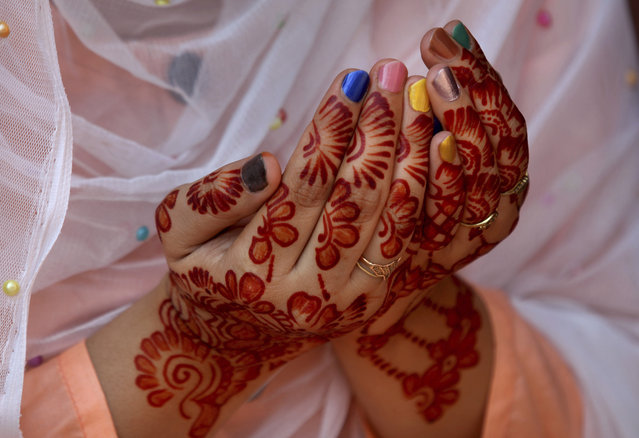 A woman, her hands decorated with traditional henna, prays during Eid al-Fitr prayer at historical Badshahi mosque in Lahore, Pakistan, Sunday, May 24, 2020. (Photo by K.M. Chaudary/AP Photo)