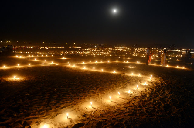 Indian devotees walk at Sangam during the 'Dev Deepawali' festival in Allahabad on November 25, 2015. 'Dev Deepawali' is observed on the full moon day (Purnima) in the month of Kartik in a traditional Hindu calendar and is the Diwali of the Devas or Gods. (Photo by Sanjay Kanojia/AFP Photo)