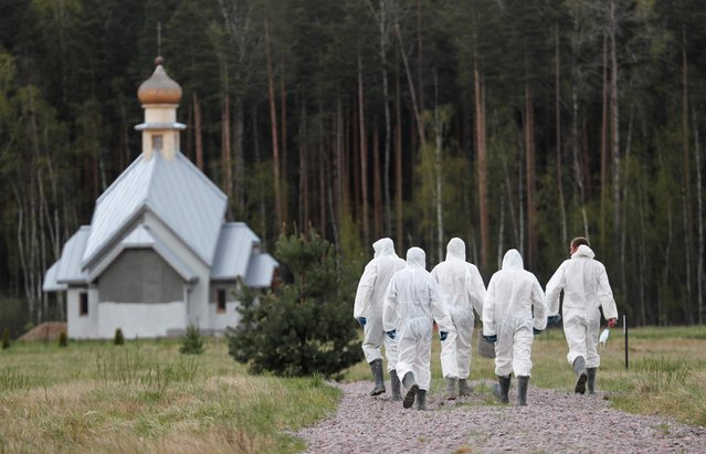 Grave diggers wearing personal protective equipment (PPE) walk away after burying a person, who presumably died of the coronavirus disease (COVID-19), in the special purpose section of a graveyard on the outskirts of Saint Petersburg, Russia on May 13, 2020. (Photo by Anton Vaganov/Reuters)