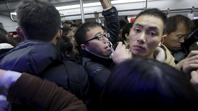 An Zi, is squashed amongst other commuters in a subway train on his way to work in Beijing, China, November 12, 2015. An, a movie producer, moved to Dongsanqi village in Changping this year. His commute to work can take about 2 hours, with transportation costs topping 200 yuan a month, or about a fifth of his monthly rent. (Photo by Jason Lee/Reuters)