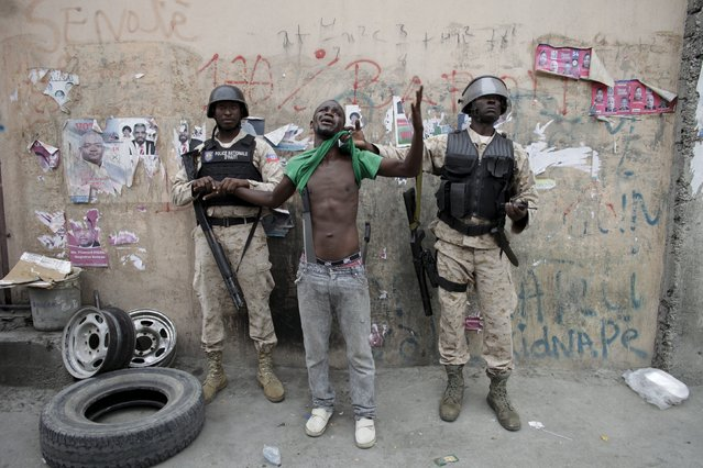 Two National Police officers guard a detained protester carrying two machetes, during a demonstration against the results of the presidential elections in Port-au-Prince, Haiti, November 26, 2015. Haiti's Provisional Electoral Council (CEP) confirmed that government-backed candidate Jovenel Moise will face Jude Celestin, the former head of Haiti's state construction company, in a runoff vote next month. (Photo by Andres Martinez Casares/Reuters)