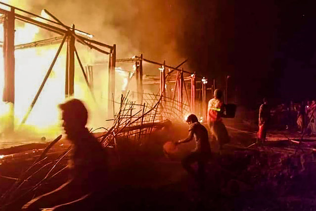 This photograph taken on January 18, 2021, shows a Unicef learning center burning down in an arson attack, at a Rohingya camp in Bangladesh's southeastern district of Cox's Bazar. Unicef has said four of its schools in a Rohingya camp in Bangladesh's southeast were burnt down in an arson attack just less than a week after hundreds of refugee homes were burnt down, officials said on January 19. (Photo by AFP Photo/Stringer)