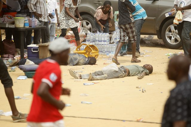 A gang member lies injured on a dusty field after a fight between rival gangs at a campaign rally for the governorship candidate of All Progressives Congress (APC) Akinwunmi Ambode in Oworonshoki district in Lagos January 19, 2015. (Photo by Akintunde Akinleye/Reuters)