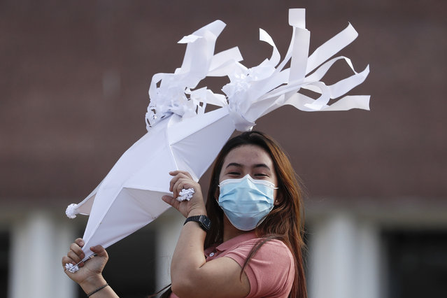 A woman wearing a mask to prevent the spread of the coronavirus holds a Christmas lantern as she assembles a display in Quezon city, Philippines on Tuesday, November 24, 2020. Philippine Officials say about 60 million Filipinos are being targeted for vaccination against the coronavirus next year at a cost of more than 73 billion pesos ($1.4 billion) to develop considerable immunity among a majority of Filipinos. (Photo by Aaron Favila/AP Photo)