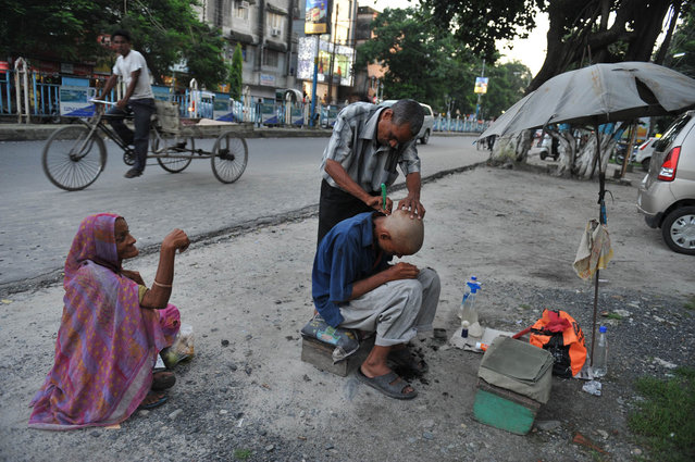 An Indian barber attends to a customer at his roadside stall in Siliguri on July 1, 2013. (Photo by Diptendu Dutta/AFP Photo)