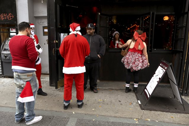 Revelers dressed in Santa Claus and other holiday themed outfits take part in the annual SantaCon event in the Brooklyn borough of New York, December 12, 2015. (Photo by Brendan McDermid/Reuters)
